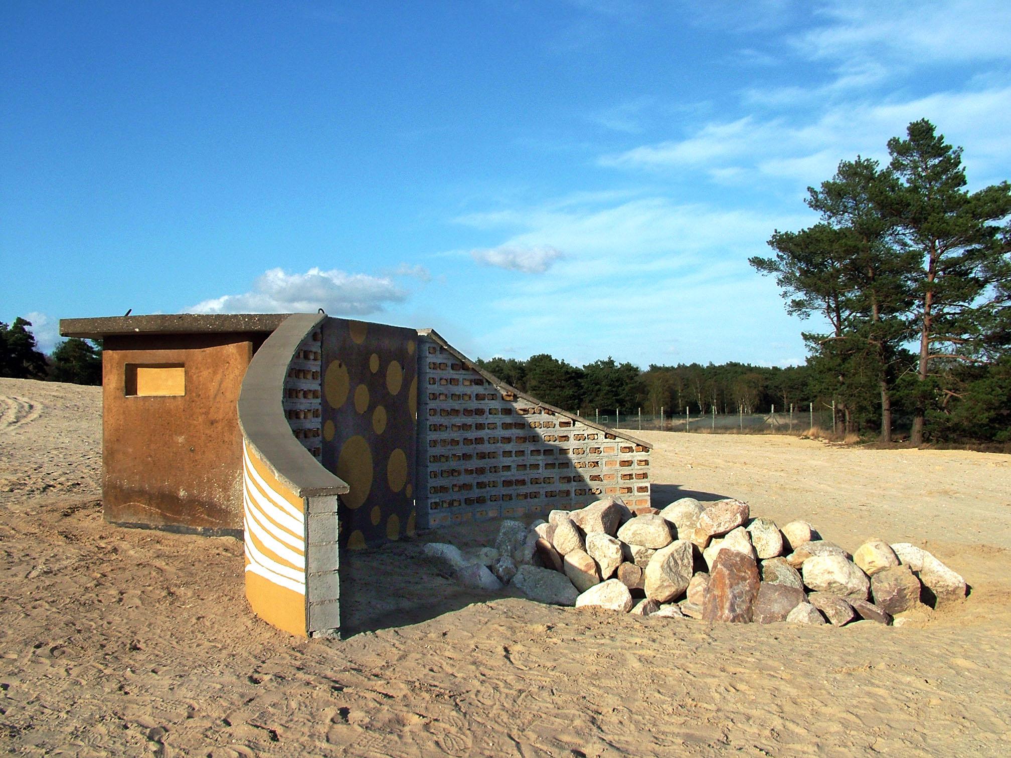 """""""Bijenhotel en meer"""" uit zich hier in het wachthuis links als kraamkamer voor vleermuizen en verblijf voor padden, en de steenhoop rechts voor adders en zandhagedissen."""